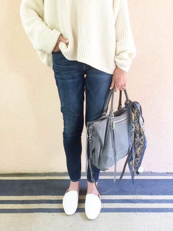 oversized white sweater with jeans and a blue handbag