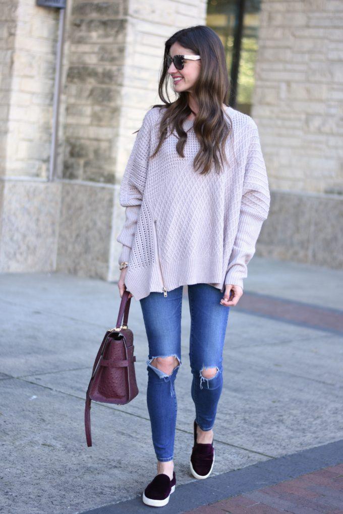 oversized sweater, asymetrical zip sweater, distressed jeans, burgundy handbag, burgundy velvet slippers