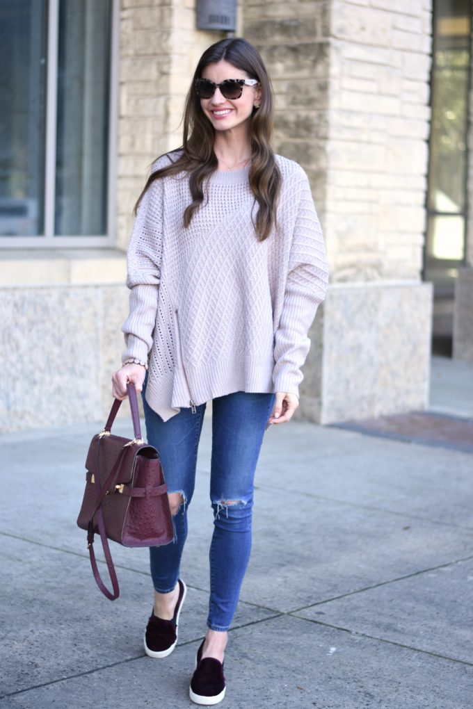 light purple oversized sweater with distressed jeans and a burgundy handbag