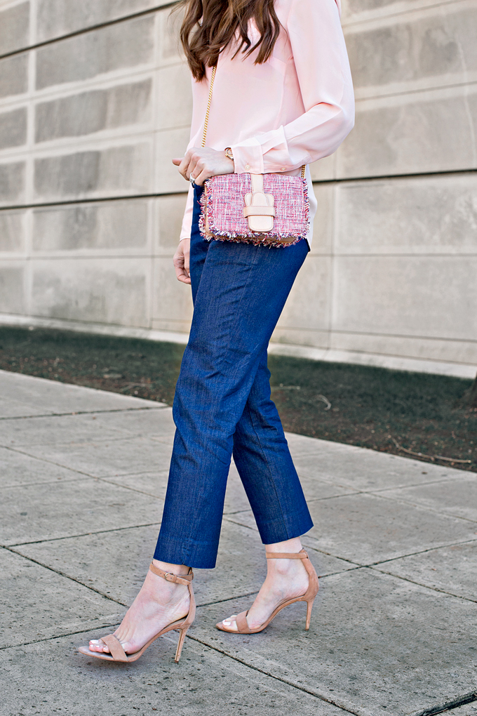denim dress pants with heels and a pale pink top and tweed handbag