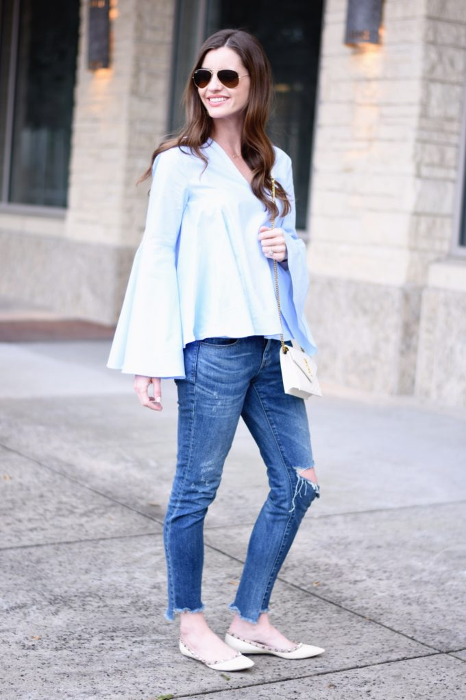 blue bell sleeve top, white cross body bag, distressed jeans