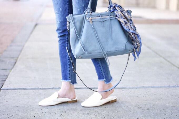 blue suede handbag and white slide loafers