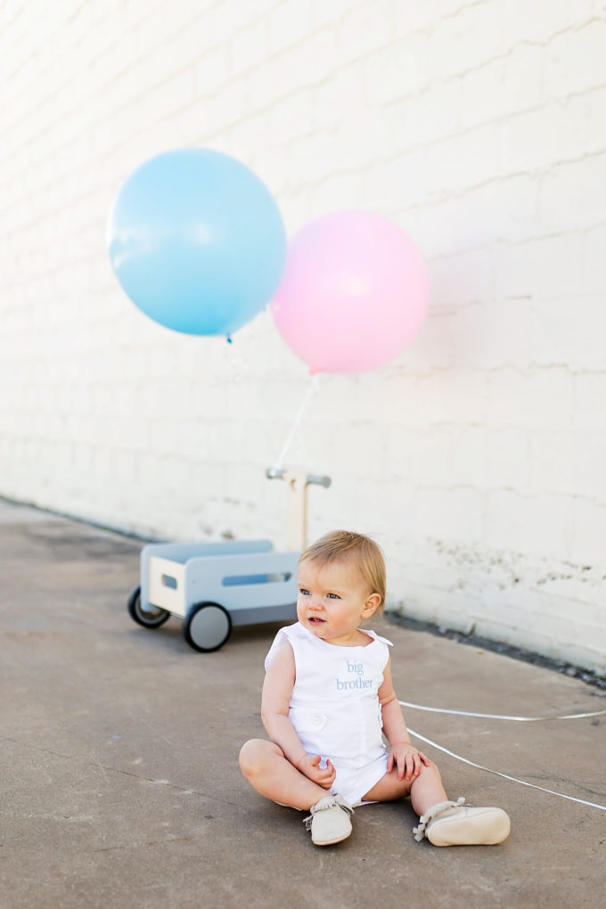 baby sitting on sidewalk with wagon and blue and pink balloons in background
