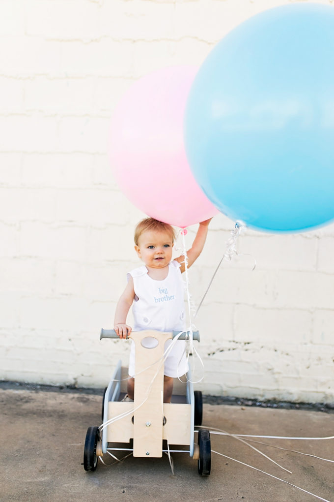 baby standing in wagon with blue and pink balloons