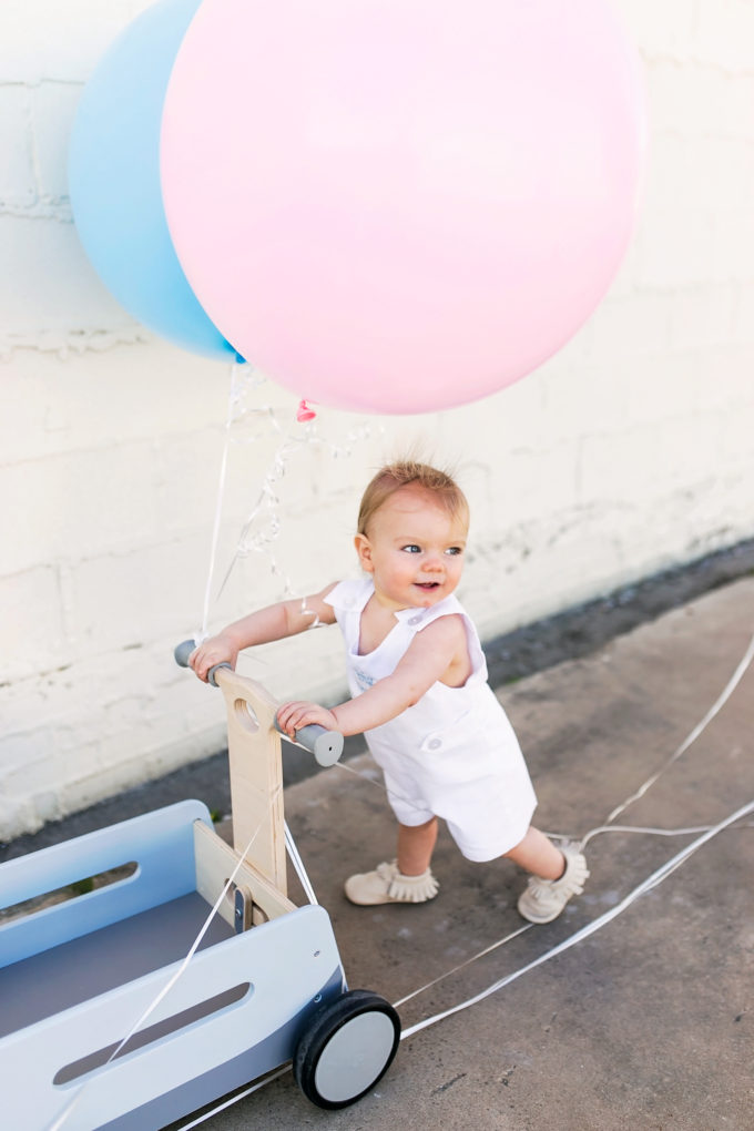 baby pushing wagon with blue and pink balloons