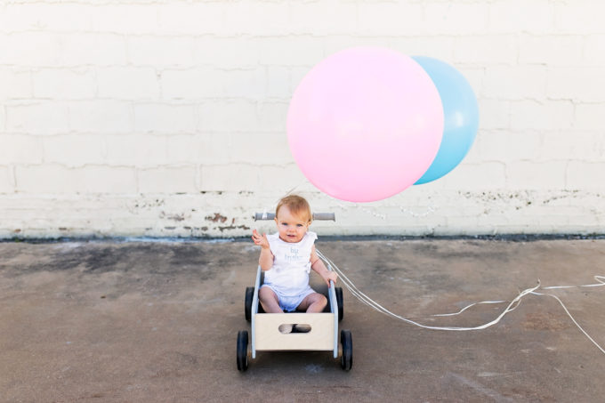 baby sitting in wagon with blue and pink balloons
