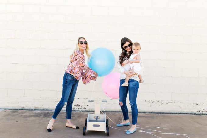 two women holding a baby and blue and pink balloons