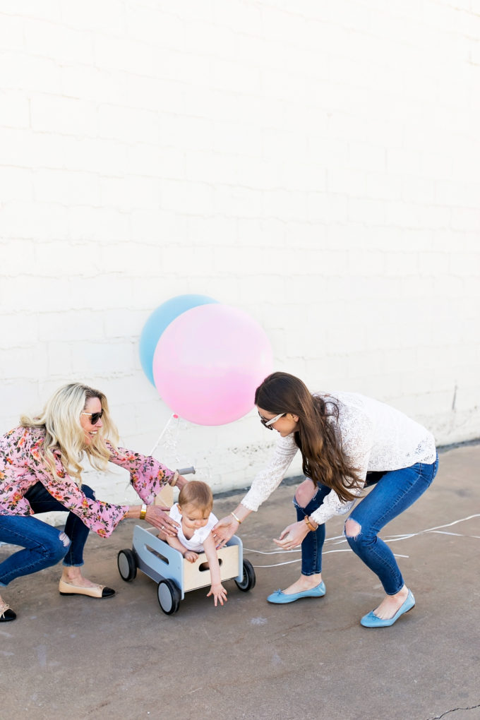 two women trying to put baby in wagon