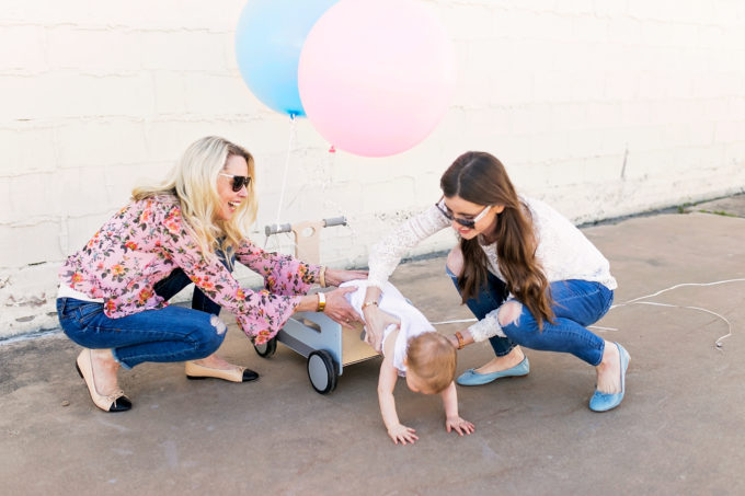 two women trying to put baby in a wagon