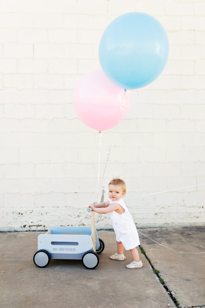 baby pushing blue wagon