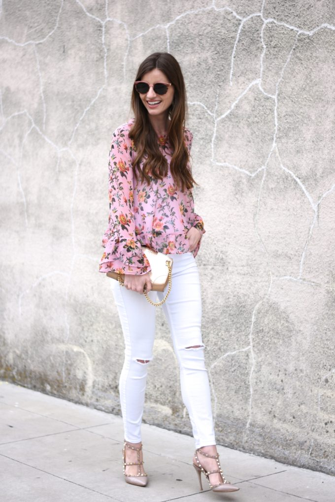 floral top with ruffle sleeves and hem, distressed white jeans, gold clutch, rockstud heels