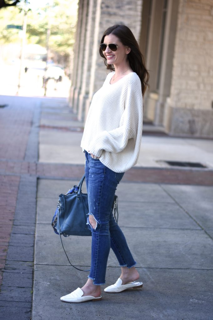 white oversized sweater, distressed jeans, blue suede handbag