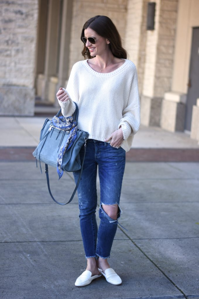 white sweater, distressed jeans, blue handbag