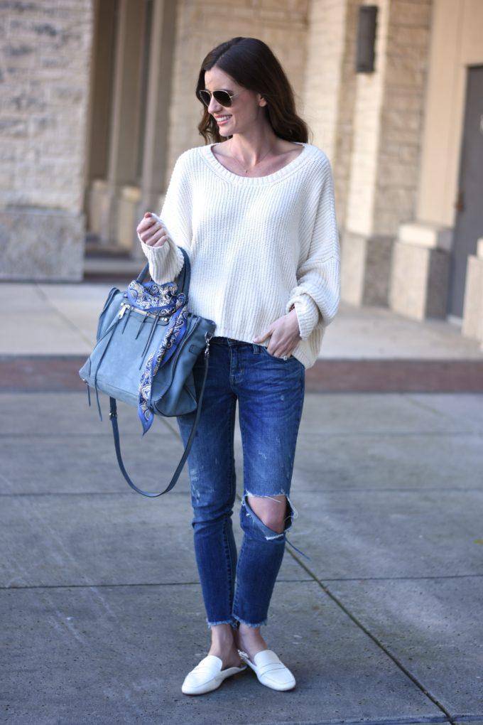 white sweater, distressed jeans, blue handbag