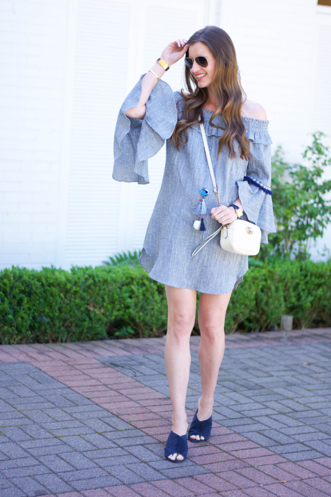 blue dress with bell sleeves, white crossbody bag