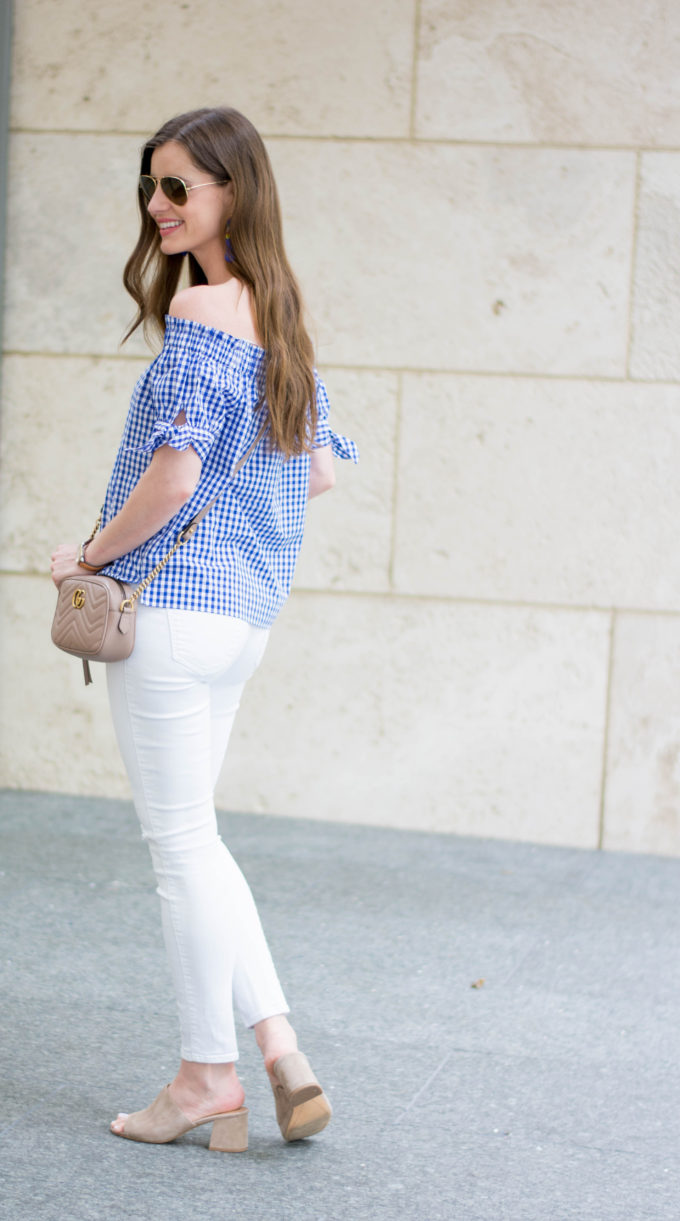 blue and white off the shoulder top, tan cross body bag, white denim