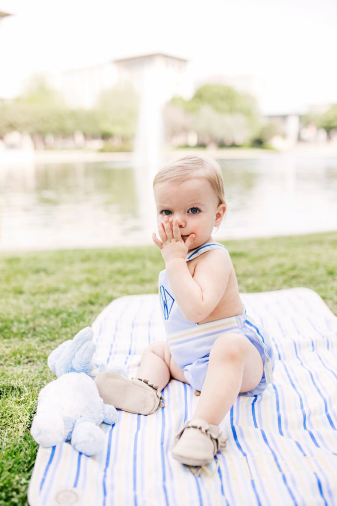 baby boy on blanket by lake