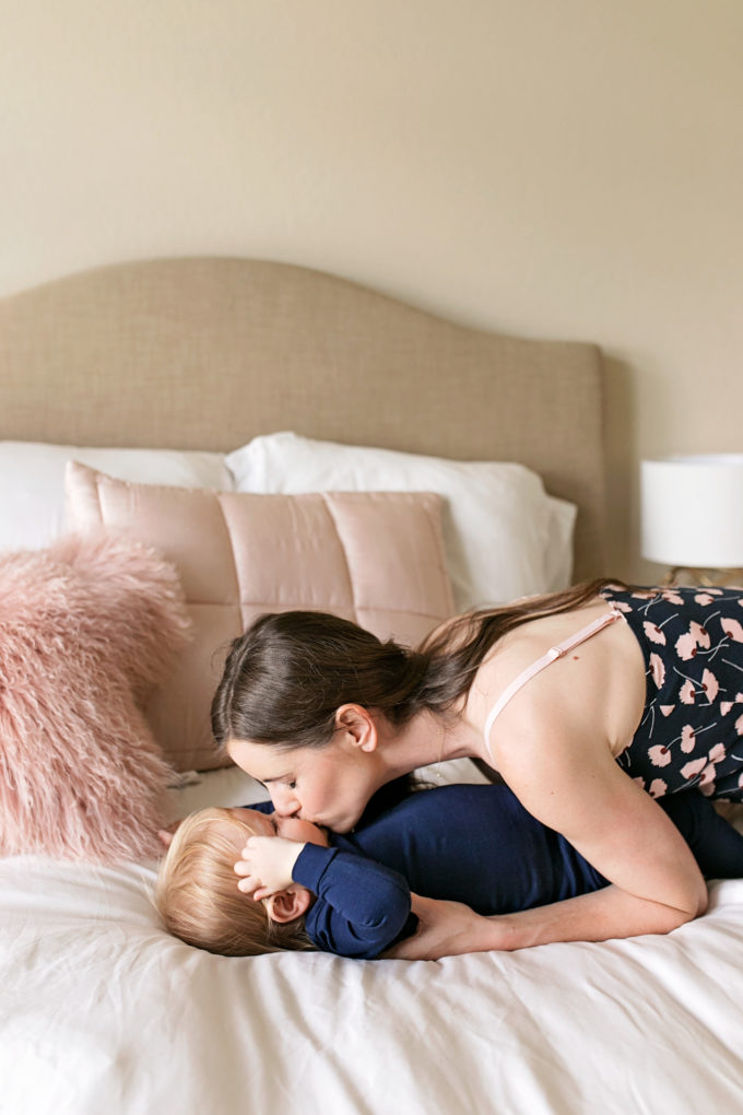 mom kissing baby on bed