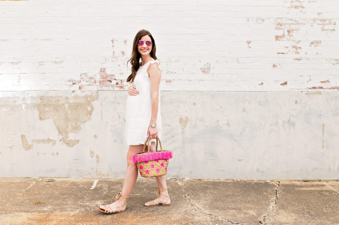 white mini dress, straw tote bag with hot pink fringe
