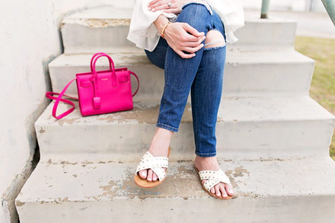 pink handbag white slide sandals distressed jeans