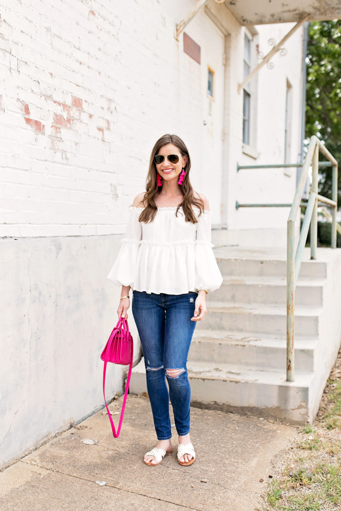 white off the shoulder top distressed jeans pink handbag