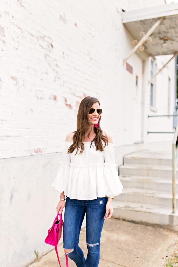 white off the shoulder top jeans hot pink hnadbag