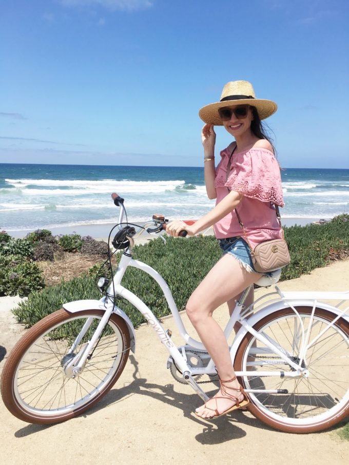 girl riding vintage bike by the beach