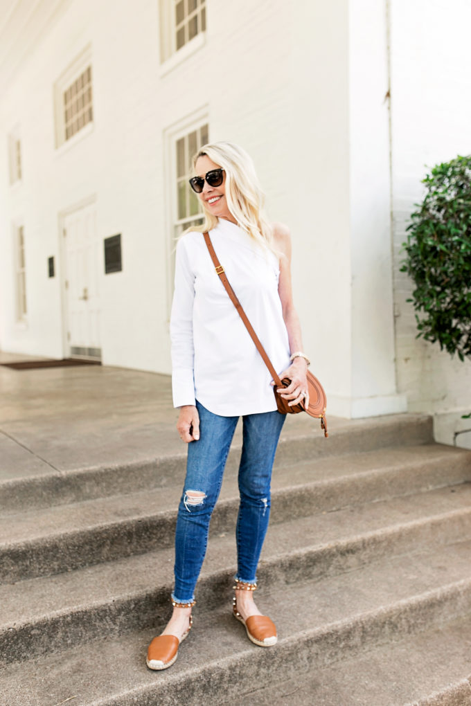 menswear inspired white one shoulder top brown crossbody bag distressed jeans