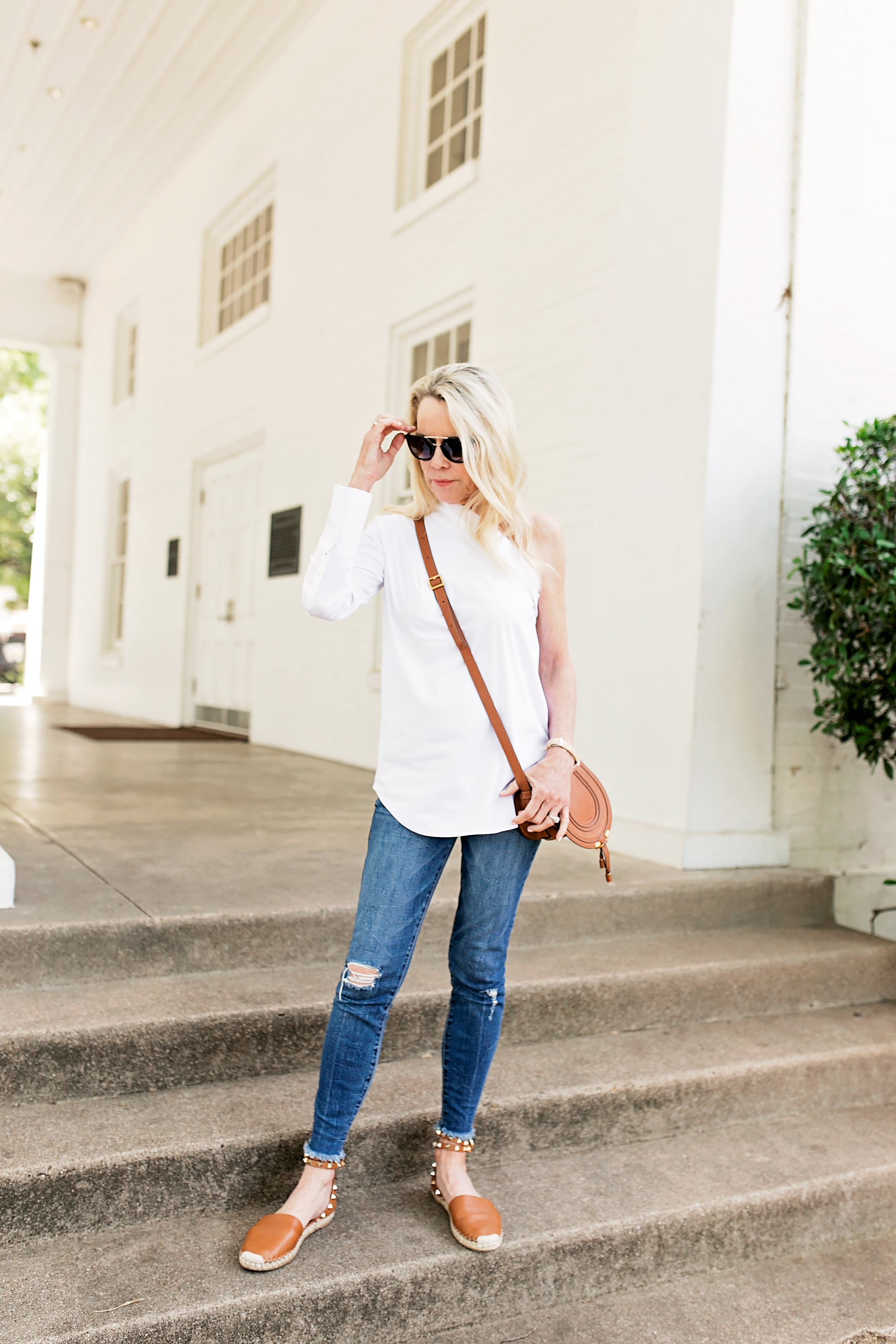 white one shoulder dress shirt brown crassbody handbag distressed jeans