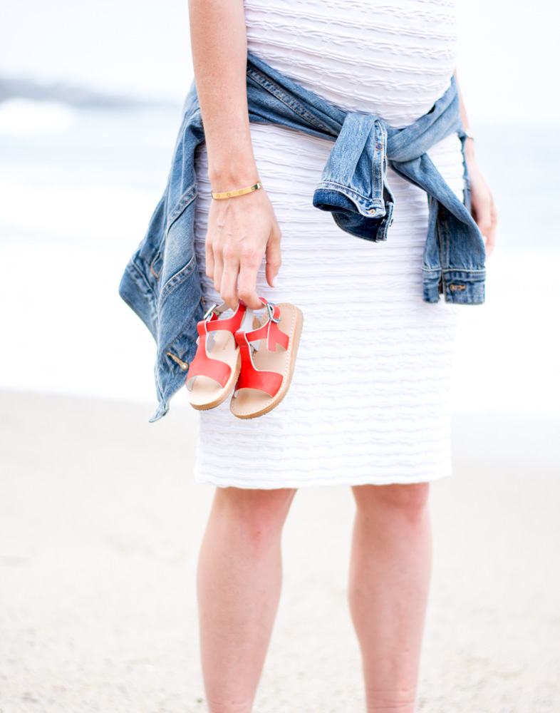 holding red toddler sandals