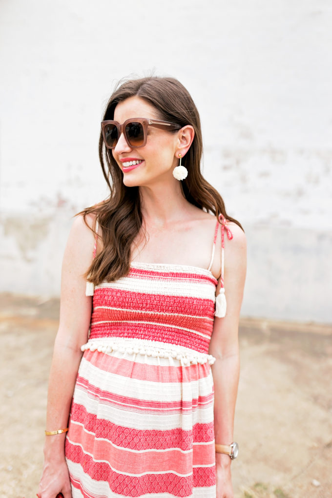 red and white dress with tassel ties, pom pom earrings over sized sunglasses