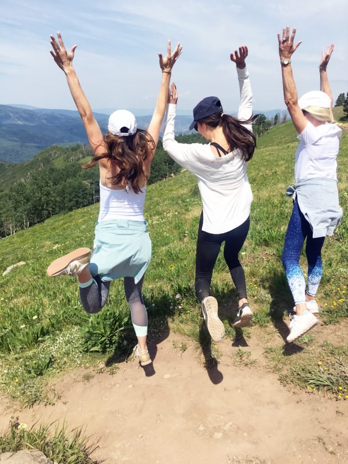 three women jumping at the top of vail mountain