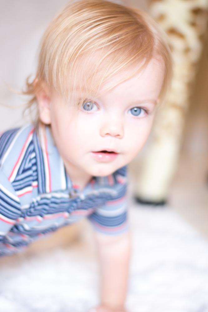blue-eyed baby boy in striped romper