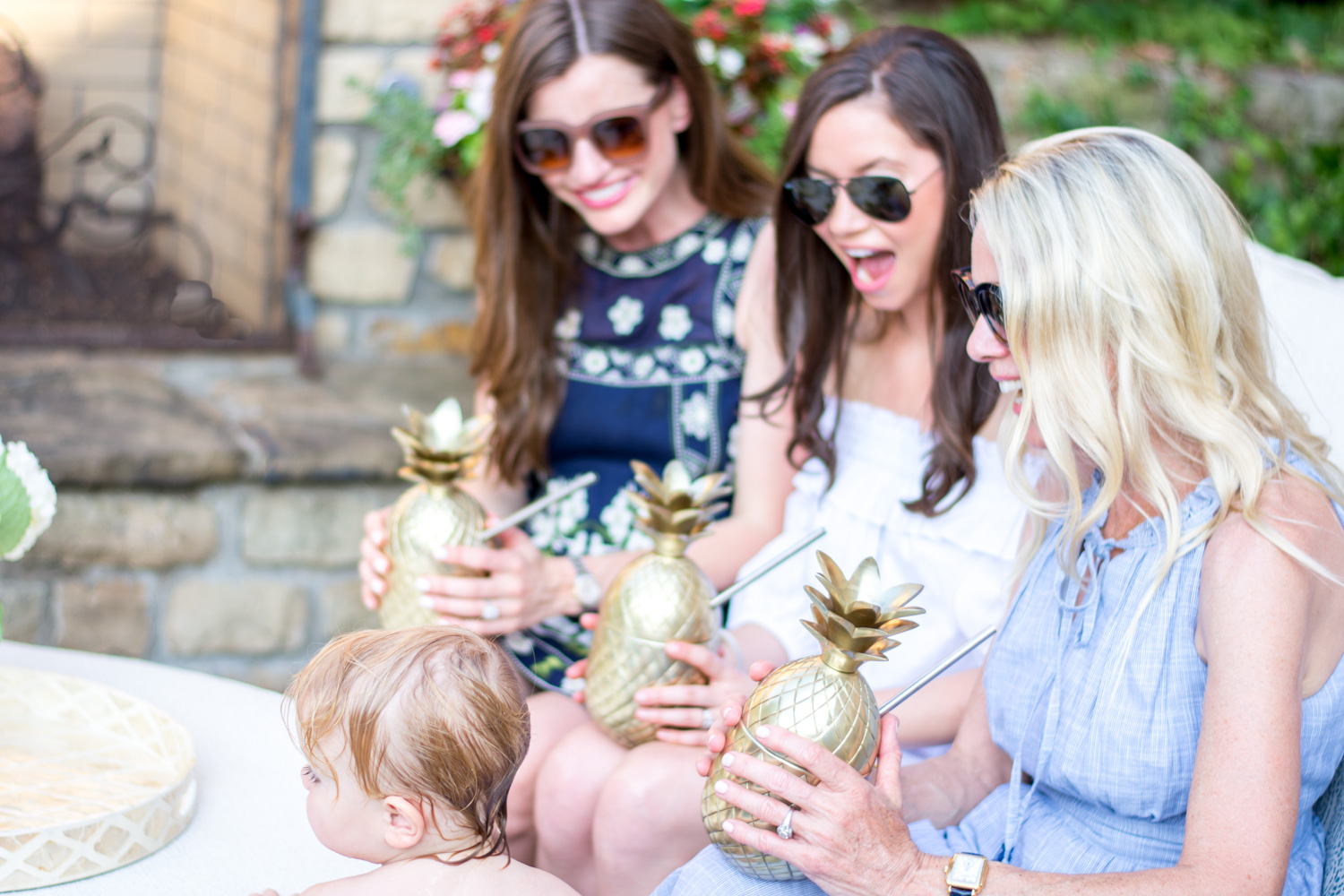 three women surprised by toddler at a poolside party