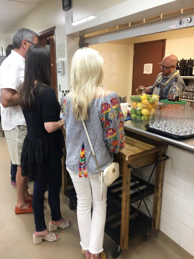 a group watching bartender mix drinks