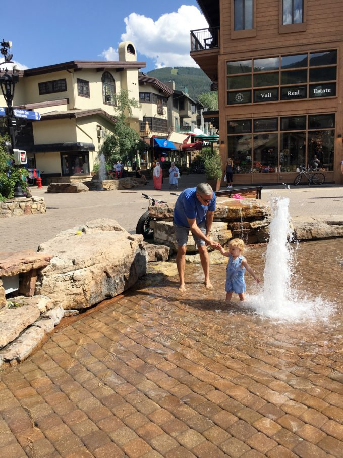 man and baby playing in fountain in vail