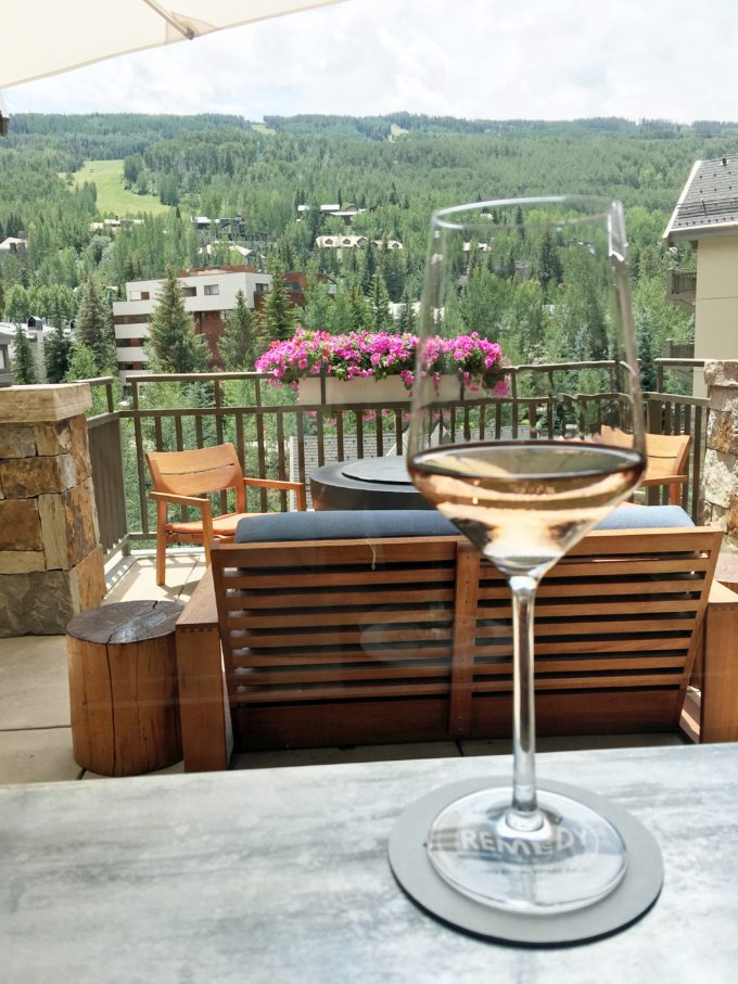 a glass of rose with view of vail mountain