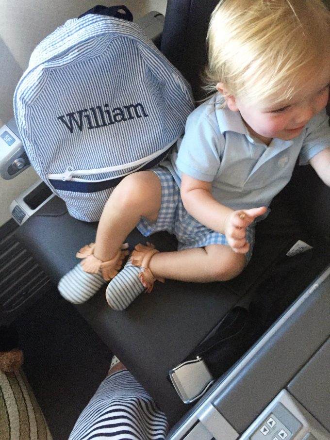 baby boy with backpack in airplane seat