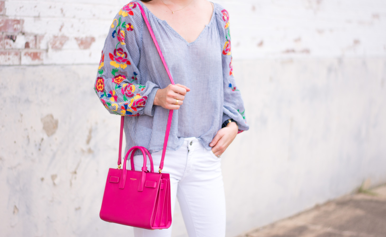 embroidered top with white jeans and hot pink handbag