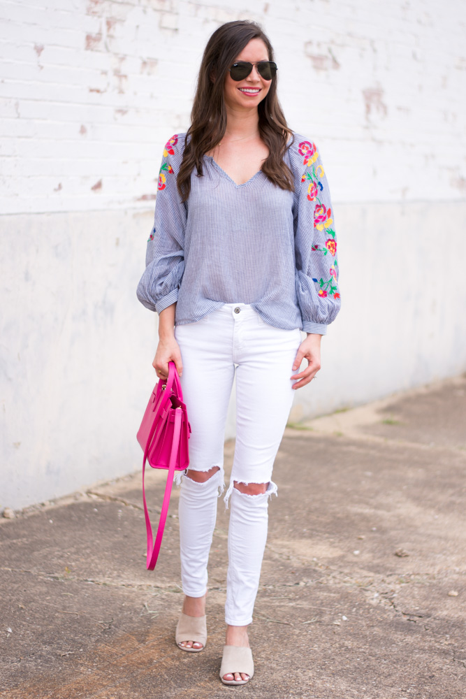 embroiered top with white jeans and hot pink handbag