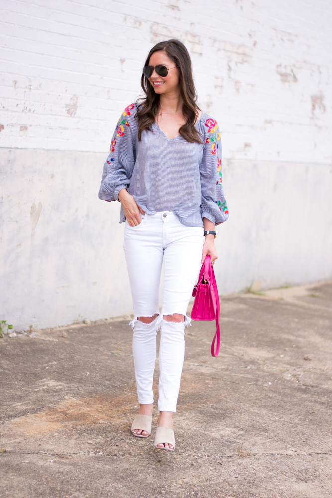 embroidered top with white jeans and hot pink cross body bag