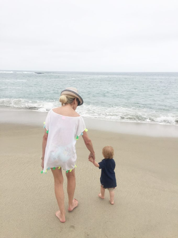 woman walking on the beach with baby boy