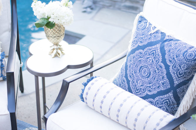 outdoor lounge chair with blue print pillow and small side table