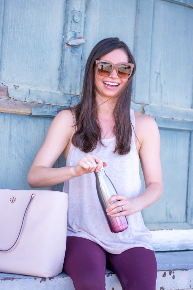 woman laughing while opening silver burgundy water bottle