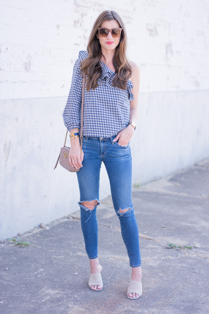 one shoulder gingham top with distressed jeans nude handbag and mules