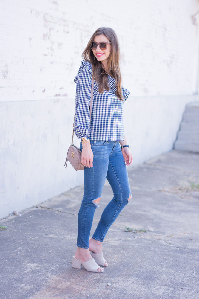 gingham top with distressed jeans nude handbag and mules