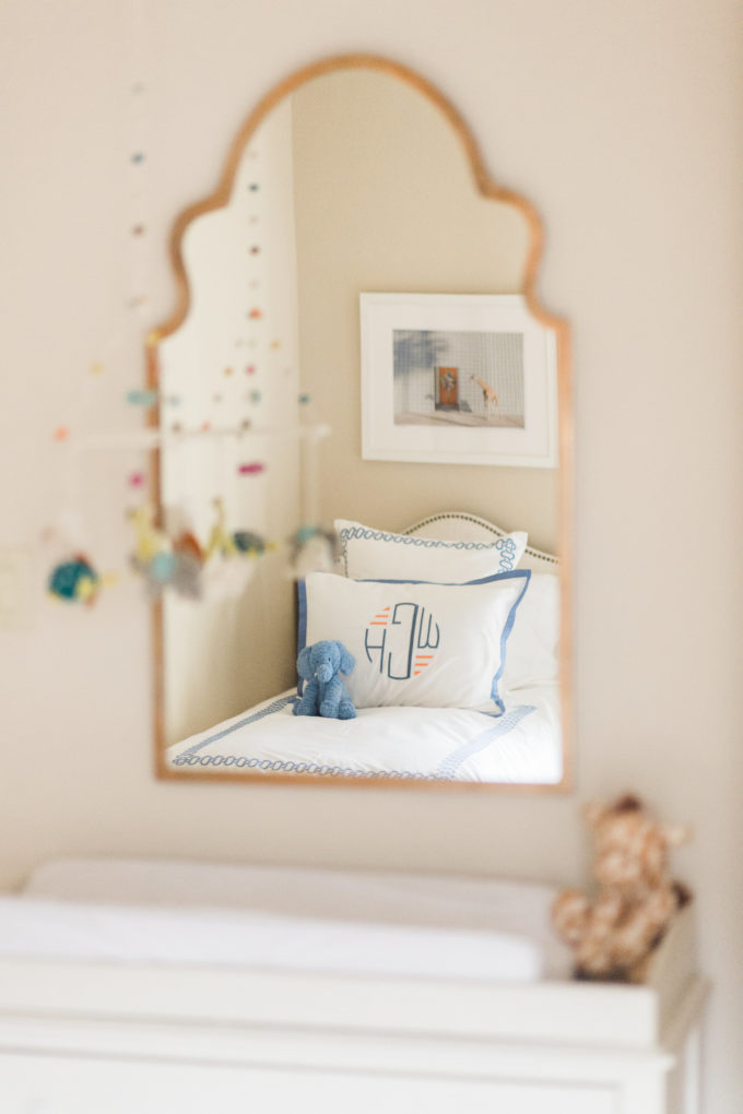 nursery mirror reflecting toddler bed