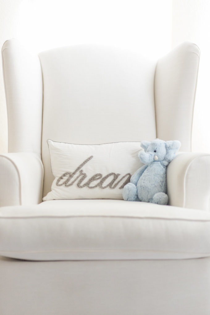 white glider for nursery with dream pillow and blue stuffed animal