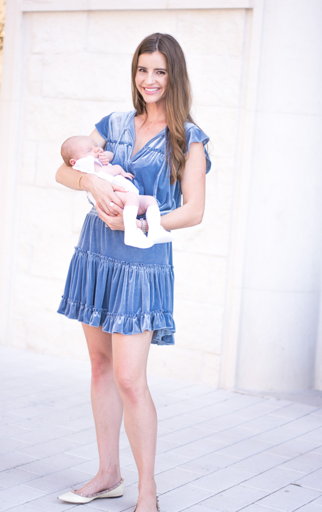 mother in blue velvet dress with baby dressed for baby dedication
