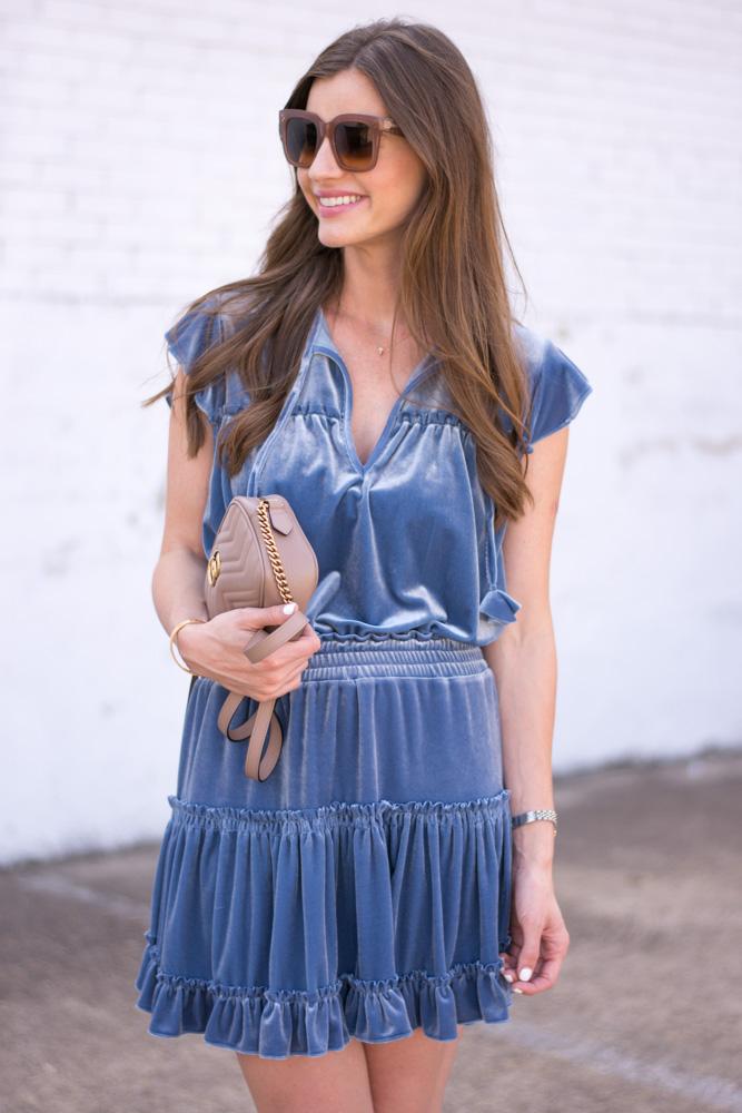 blue velvet dress neutral handbag
